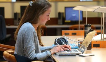 A student studying in Stauffer Library, on the main floor