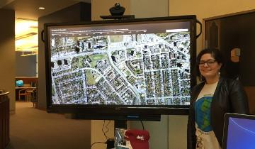 Librarian standing with screen displaying map