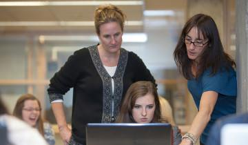 staff helping student at computer